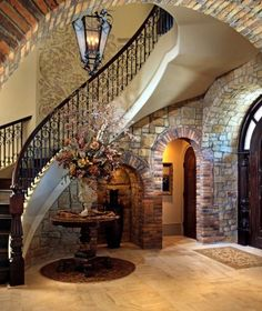 Imagine this as a double courved staircase with wrought iron railings, deep wood stained top railing, steps, and posts, step risers with colorful Mexican painted tile, walls of Tuscan stone, arched doorway passages; perfection.