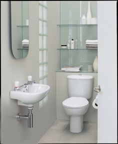 Clever Glass Shelving can make all the difference in a small bathroom suite, glass reflects light so give a feeling of space as well as housing any necessary clutter! Put up venetian blinds and then consider a glass shelf or two in the window as well. Small Bathroom Suites, Small Bathroom Vanities, Bathrooms, Bathroom Bath, Industrial Bathroom Vanity, Bathroom Vanity Storage, Downstairs Cloakroom, Downstairs Toilet, Toilet Room