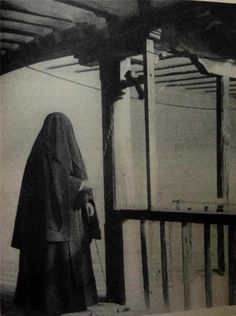Carmelite with face veiled ringing bell to warn fellow nuns to stay in cell or veil their faces due to a male being in the cloister
