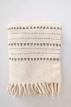 Snuggle up this winter with our handwoven natural wool blanket with black embroidery.