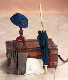 """Theriault's Antique Doll Auctions - Accessories for Lady Dolls - Comprising an 8"""" bone-handled parasol with bone tip and bone tine tips,and having (frail) navy blue silk cover; blue silk bonnet with draped banding and silver decoration in the shape of a stylized bird; 2 """"l. kidskin gloves in grey taupe color; and lace-edged monograph embroidered """"G"""". Circa 1875."""