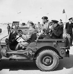 Winston Churchill lights a cigar in the back of a jeep as he and General Montgomery, commanding 21st Army Group, set out on a tour of the Normandy landing beaches, 12 June 1944.