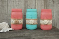 3 quart size mason jars hand painted in coral and aqua with a ribbon of burlap and lace, and a burlap flower, lightly distressed with a protective coating. They
