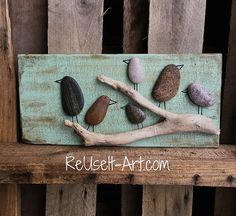 ReUse It Art™ handcrafts & upcycles wooden pallets into stunning wall decor. Wood signs may be fully customized. Seaglass, river rock, wine corks and driftwood may also be found in our one of a kind creations. All original wood pieces are crafted with care and pride. I make each piece as if it were my own. Rock Art Wood Sign Details:  - Distressed Green background with Rocks in shape of Birds standing in a tree made from a piece of driftwood. - Rocks are safely and permanently adhered using…