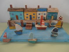 Four Harbour Cottages.  I made this from wood/driftwood washed up on the beach and used Sea pottery for the sails. By Sea side art design by Philippa Komercharo. FB page.