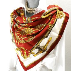A gorgeous vintage Hermès scarf Roues De Canon by Caty Latham first issued in 1967, here in a delicious color combination of maroon accented by vibrant golds framed by a cool off white. Another authen