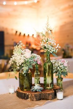 Rustic wedding centerpiece idea - vintage bottles with pink and white flower arrangements on a wooden slice {Christopher Helm Photography}