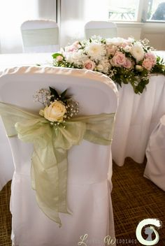 Single ivory rose with gypsophila placed in the chair bow