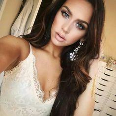 bridal makeup look. glowy skin. nude lip color. smoky eyes. long, brown hair. brunette. statement jewelry. loose curls hairstyle.