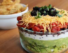 Healthy Seven-Layer Dip ~ 2 cups chopped romaine lettuce, 2 avocados, mashed well, 1 cup low-fat Greek yogurt, 2/3 cup black beans, 1/2 cup diced tomatoes, 1/2 cup shredded cheddar cheese, Sliced black olives, and scallions to garnish.