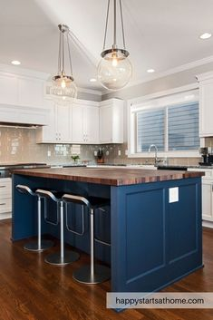 This bright white kitchen has white cabinets and grey quartz counter with a grey glass tile backsplash. We also added this navy kitchen island topped with a butcher block counter. We hope this navy and white kitchen inspires your decor! inspires#butcherblockcounter #navykitchen