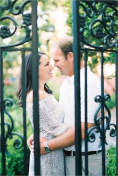 Creative engagement photo of couple shot through a gate at College of Charleston by Catherine Ann Photography | Portra 400 film