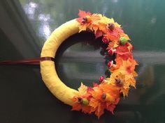Herfstkrans gemaakt door een reep gele stof over een strokrans te wikkelen.  Aan de onderkant voorgestanste bladeren van de xenos. En daarop zelfgemaakte vilten eikeltjes.