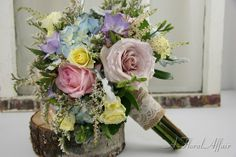 Blue hydrangea; pink, champaign and yellow roses; lavender freesia; white misty and pink astilbe; with dusty miller accents create a beautiful bouquet.  It's perfect for country, rustic, and vintage themed weddings.  Flowers by A Floral Affair - www.afloralaffair.com #pdxweddings #weddingbouquet