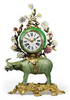 A FRENCH ORMOLU, CHINESE AND EUROPEAN PORCELAIN MANTEL CLOCK. MID-18TH CENTURY AND LATER, THE CELADON BUFFALO LATE QING DYNASTY (1644-1912)