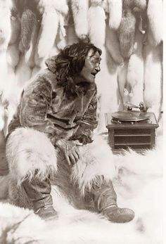 An Eskimo man enjoying some music on a record player, 1922