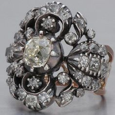 This antique Georgian Engagement Ring with old mine-cut diamonds is crafted in silver-topped 18k rose gold.