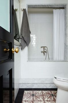 A black door leads into a bathroom covered in white subway tiles and squid-patterned floor tiles.