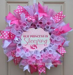 This beautiful pink baby girl deco mesh wreath will let guests know your precious little one is sleeping! This wreath measures 24 in diameter and is constructed out of metallic pink and white deco mesh. It is accented throughout with pink and white wired ribbon. In the center is an adorable wood sign that reads, Shhh... Our Princess is Sleeping. This wreath would be perfect for new parents, for a baby shower gift, or to hang on a hospital door! This wreath is also available in blue for…