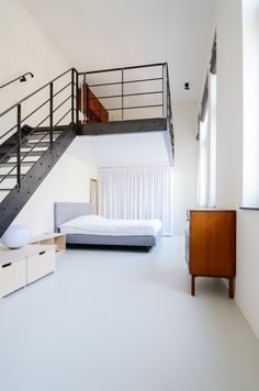 Once a teacher's lounge, the master bedroom now occupies the first-floor space. A hot rolled steel staircase leads to the lofted second-floor, an addition which brought more livable square footage to the overall program.