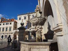 Fonte na praça das muralhas e ao fundo as casas de moradia -Dubrovnik