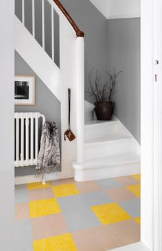 Cool look in the entryway with half-painted grey walls and a graphic nice floor of coloured tiles.