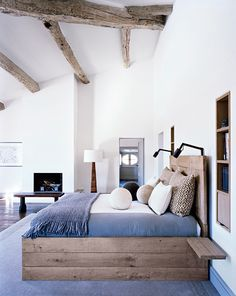 Exposed wood on ceiling, bed base, fireplace, dark wood floors, book shelf in wall