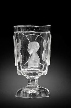 A fine North Bohemian engraved triple-portrait goblet by Dominik Biemann, Franzensbad, dated 1849   --   Signed, the slightly flared cylindrical bowl with three raised oval medallions, each decorated with an intaglio bust portrait of a child to dexter, set on a an hexagonal stem and foot, inscribed on the base Franzensbad 1849
