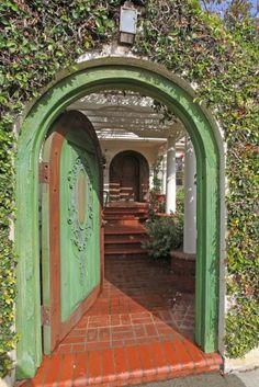 #SpanishCourtyard Beautiful antique door with green paint and boxwood vines.  #GardenGate #MediteranneanStyleHome. Beautiful Green Door.  Inviting.