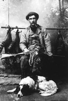 A hunter sitting with pelts and a rifle in his lap, his dog at his feet and racoons strung up behind him. Photograph by Wallace G. Levison. USA, 1890.