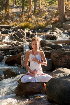 yoga pose outdoors in the woods sitting on a boulder in a wild creek.  Copyright:Elena Ray 2012