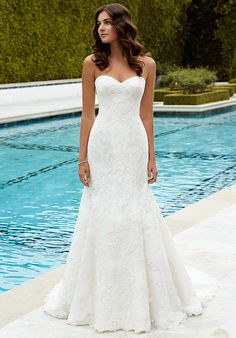Full-length, tulle mermaid gown with a romantic sweetheart neckline, intricately re-embroidered lace over corded lace appliques, and seamless center back zipper.