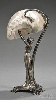Art Nouveau Silver-plate and Mother-of-pearl Figural Lamp, Germany, late century, mark of Wurttembergische Metallwarenfabrik (WMF), the base formed as a scantily clad nymph reaching upward towards the shade formed by a large nautilus shell. Mobiliário Art Nouveau, Art Nouveau Design, Muebles Estilo Art Nouveau, Lampe Art Deco, Jugendstil Design, Art Nouveau Furniture, Art Ancien, Nautilus Shell, Antique Lamps