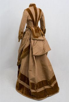 There are two parts to the dress: a bodice and a layered skirt. It was common in the early 1870s for skirts to have two separate layers. In this case, the layers are both attached together at the waist. The dress retains design elements of the 1860s: the dropped shoulder; the narrow corded piping around the armholes; and the use of silk fringe.