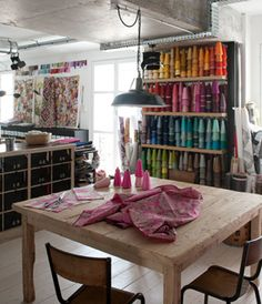 We love this studio space with it's wall of brightly colored fiberart supplies. A large table allows ample space for working on your latest interior design projects.