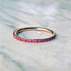 Pink sapphire eternity ring, available in 18k rose gold and 18k yellow gold, set with vivid pink brilliant cut sapphires.