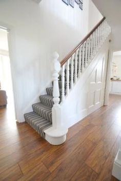 dark wood downstairs with stripy hall carpet and white walls