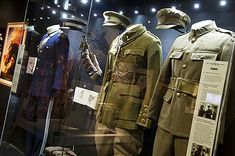 a photo of military uniforms in a display case