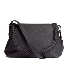 Small shoulder bag in imitation leather with a detachable, adjustable shoulder strap. Flap with braided details and magnetic closure, and one inner compartment with zip. Lined. Size 9 x 12 1/4 in.