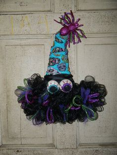 I have up for sale a Handmade Halloween Witch Hat Door Décor This one is made of Light Blue/Greeny Skull Material Scarf background with black deco mesh. Accented with purple and lime green tubing and more. Has a Black Wide ribbon around the hat Has Halloween Witch Wreath, Halloween Mesh Wreaths, Halloween Ribbon, Halloween Magic, Halloween Door Decorations, Halloween Hats, Holiday Wreaths, Scarecrow Wreath, Halloween Witches