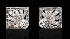 A PAIR OF DIAMOND CUFFLINKS   Each single-link of square outline, set with a circular-cut diamond, enhanced by circular-cut diamond rays, with baguette-cut diamond trim, mounted in platinum and 14K white gold. Art Deco or Art Deco style.