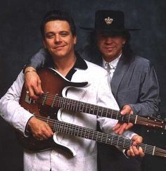 Jimmy and Stevie Ray Vaughan posing with a Danelectro longhorn double neck