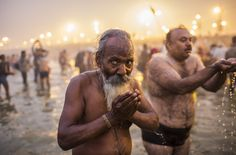 Hindu devotees bathe in the waters of the holy Ganges river during the Maha Kumbh Mela in Allahabad, on January 14, 2013. (Daniel Berehulak/Getty Images)