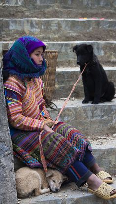 A Hmong girl is sitting on the stairs at the Bac Ha market near Sapa, Vietnam while holding her white and black dogs. Click through to find out more.