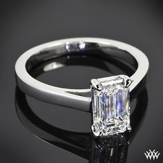 beautiful Custom Solitaire Engagement Ring is set in platinum and the 4 prong head holds a brilliant 1.53ct Emerald Cut Diamond