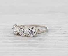 Antique Edwardian three stone ring made in platinum and centered with an EGL certified approximately .99 carat old European cut diamond with F-G color and SI1 clarity. Accented with two old European cut diamonds weighing approximately 1.66 carats total. Circa 1910. Cost $ 11,250