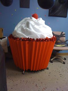 This is a giant cupcake I made out of a coworkers round table in her office. 5 red poster boards fan folded and taped together for cup, sheet batting for icing, spray painted a round styrofoam ball red and stuck tree branch in top for cherry. Sprinkle with confetti and wrapped Christmas type garland on edge of cup.