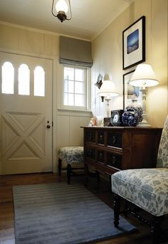 Charming Foyer    Comfortable chairs and a bureau are both pretty and practical.      Reclaimed and unstained oak floors were installed to complement the original 1920s paneling. The look is meant to mimic the soft sand on the beach just outside the cottage.