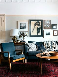 Effortlessly stylish mid century living room, with blue sofa and eames chairs and gallery wall.
