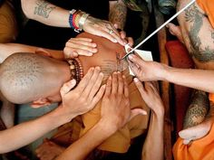 Buddhist Monk getting tattooed with prayers for spiritual protection, Thailand